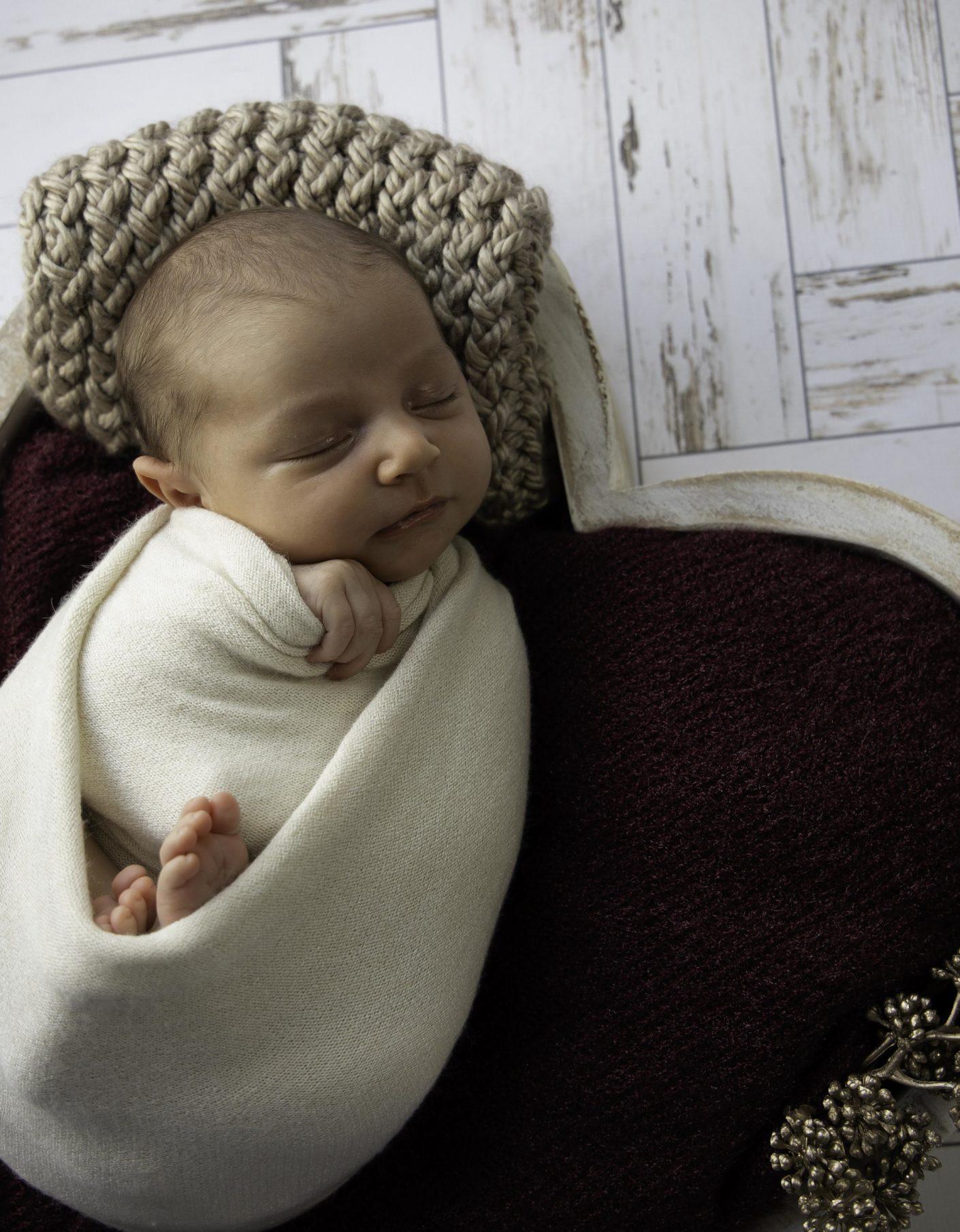 Bébé fille emmaillotée, contenant coeur